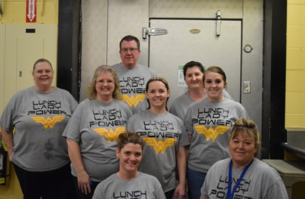 "Cafeteria workers wearing ""Lunch Lady Power"" shirts."