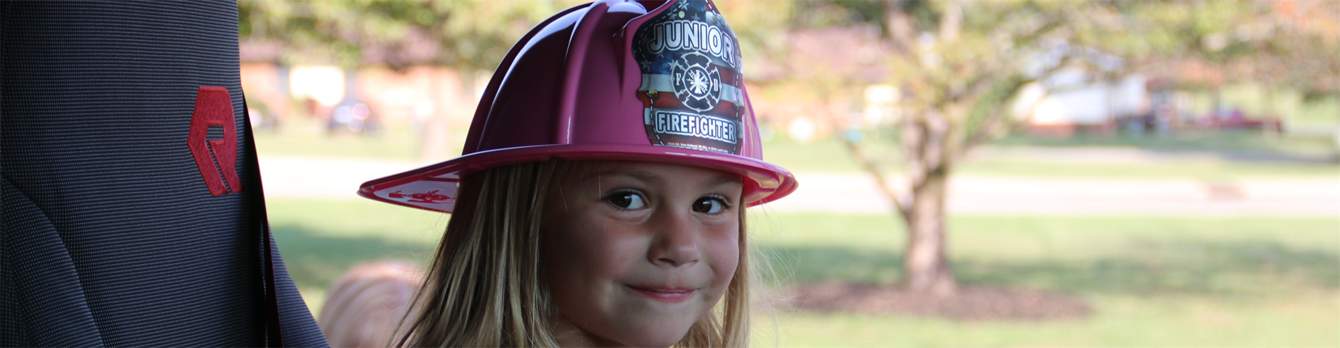 Young girl in a Fire Fighter hat.
