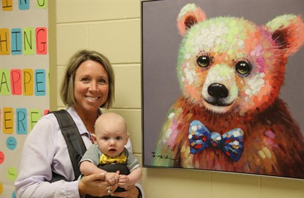 CCCDC director Leah Spencer holds an infant in a front carrier. Painting of a bear on the wall in background.