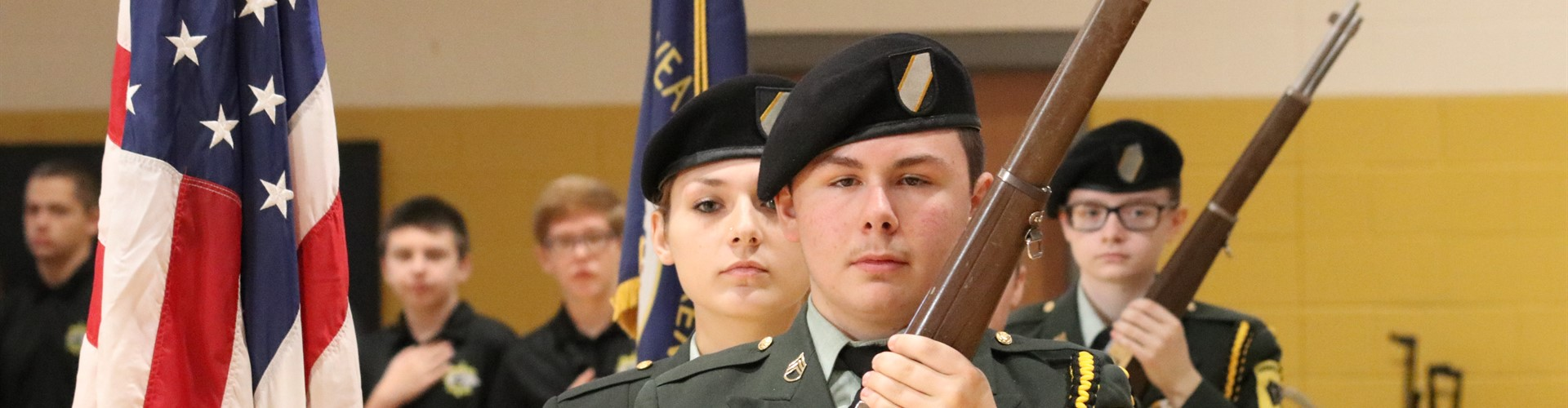 Three Honor Guard students carry ceremonial arms after posting the colors